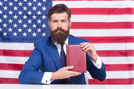 Liberty of printing. Patriotic businessman hold book on american flag blackground. American liberty. Independence day. 4th of July. Pride and liberty. Political rights and freedoms. Liberty of choice
