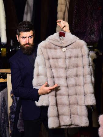 Guy holds beige furry coat in fur shop.