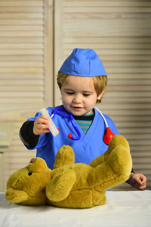 Healthcare and childhood concept. Kid in doctor coat makes injection