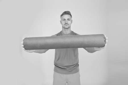 Personal training. Meditations designed to help you find your joy. Man practicing yoga at home. Handsome sportsman with yoga mat. Workouts with modifications for different levels. Yoga is my hobby