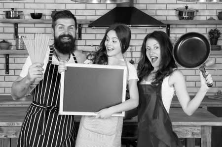 Pleasant time together. Recipe of perfect family dinner. Mother and father with little girl holding chalkboard copy space. Little girl with parents cooking. Family day. Happy family in kitchen