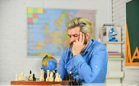 Chess Academy. Focused school teacher. thinking of attacking and capturing opponent chess pieces. thinking of next move. bearded man training for chess competition. chess figures on wooden board