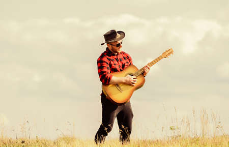 Play beautiful melody. Country music concept. Guitarist country singer stand in field sky background. Inspired country musician. Hiking song. Handsome man with guitar. Country style. Summer vacation Zdjęcie Seryjne