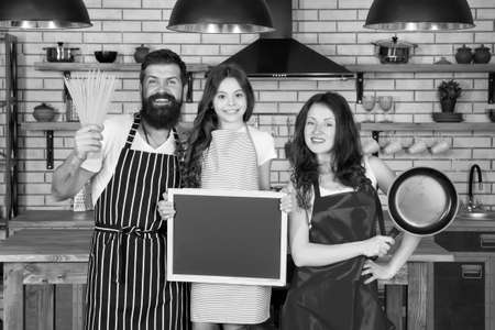 Family day. Happy family in kitchen. Pleasant time together. Recipe of perfect family dinner. Mother and father with little girl holding chalkboard copy space. Little girl with parents cooking