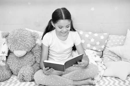 Bedtime reading fun. Happy girl read book to toy friend. Small child enjoy reading fiction story. Reading stimulates pretend play. Developing imagination. Reading makes you more creative