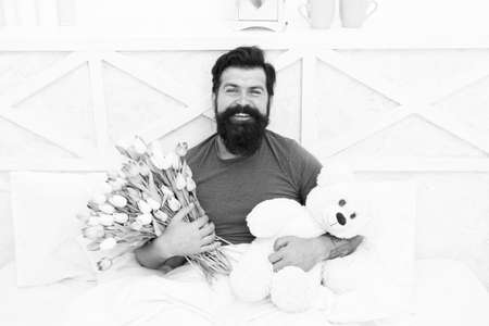 Birthday holiday. Fresh flowers. Bearded hipster in bed. Valentines day gift. Man hold bouquet relaxing in bed. Flowers delivery service. Make surprise concept. Gift for spouse. Cute teddy bear