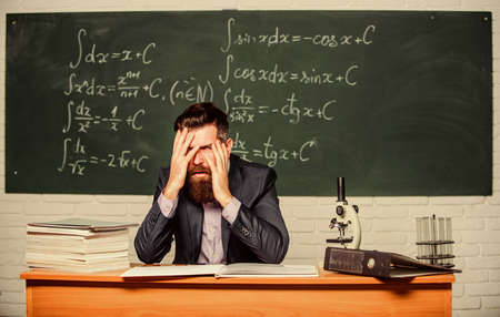 Teaching dumb students. No hope for better. Tired and exhausted. Teacher mature man. Fed up. Difficult work. Emotional burnout. Teacher give up. Hate his job. Man desperate teacher in classroom