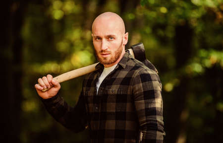 Harvest firewood. Hike vacation. Hike in forest. Forest care. Determination of human spirit. Man checkered shirt use axe. Brutal male in forest. Power and strength. Lumberjack carry ax. Bald woodsman