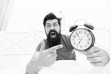 What time is it. Stressed man alarm clock. Sleepy man holding alarm clock in bed. Bearded man with alarm clock. Hipster want to sleep. Hate early morning awakening. Daily stress. Get up right now