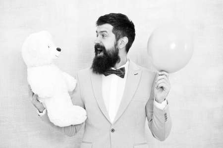 cheerful hipster in jacket and bow tie. gift for special event. ready for love date. romantic present for holiday. teddy bear and air balloon. birthday party surprise. full of happiness Archivio Fotografico