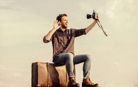 Travel blogger. Handsome guy traveler retro camera. Travel with luggage. Shooting vlog. Vacation time. Guy outdoors with vintage suitcase. Photojournalist concept. Travel blog. Man sit on suitcase