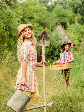 ecology and environmental protection. earth day. summer farm. child hold gardening tools. small girl farmer with shovel and watering can. happy farming. spring country side. selective focus Banque d'images