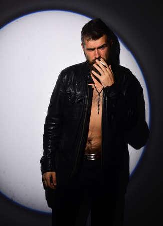 Man with beard smokes cigarette. Guy with half naked torso