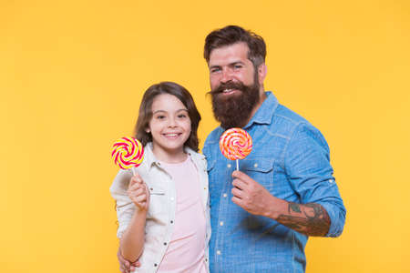 Dessert makes mouths happy. Happy family hold lollipops yellow background. Father and daughter enjoy eating dessert. Sweetshop. Candy store and confectionary. You deserve dessert today