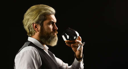 Bearded businessman in elegant suit with glass of wine.