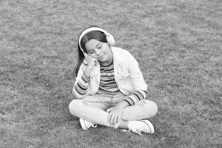 Child listen music on green grass. Healthy lifestyle and relax. Yoga girl. small kid in headphones. Imagens