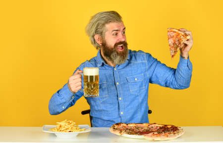 French fries. guy in bar drinking beer glass and eating pizza. Cheers. watching football on TV. american fast food. happy bearded man with beer and pizza. italian food Stock fotó