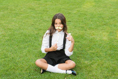 Funny party concept. Cute mustache. Small girl hold fake mustache on face. Happy childhood. Little child school uniform. Back to school. Small schoolgirl sit on green grass. Fashion accessory