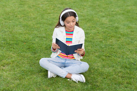 development of the imagination. cute girl read book. happy preschool girl with book in school yard. back to school. hardworking child in headphones. concept of education and reading. be a writer Imagens