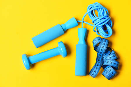 Dumbbells with centimeter and jumping rope Sports equipment in cyan blue color.