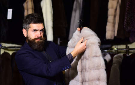 Guy holds beige furry coat with fur on background.