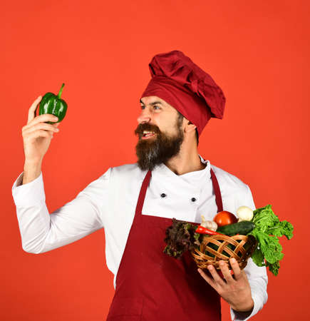 Chef holds lettuce, tomato, pepper and mushrooms.