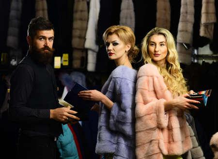 Friends in shop: ladies and gentleman try overcoats on.