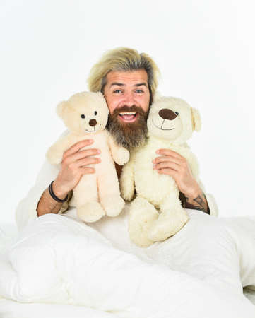 togetherness. Sick man with flu lying in the bed. sleeping at home in bed with his toy. man sleeping in embrace with white teddy bear.