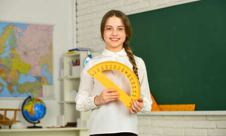 Cute little schoolgirl with geometrical tool for mathematics. Stockfoto