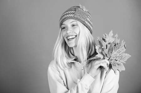 Feel happy this autumn. Woman cute face wear knitted hat hold fallen leaves. Autumn skincare tips.