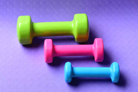 Barbells in different colors placed in pattern, top view 免版税图像