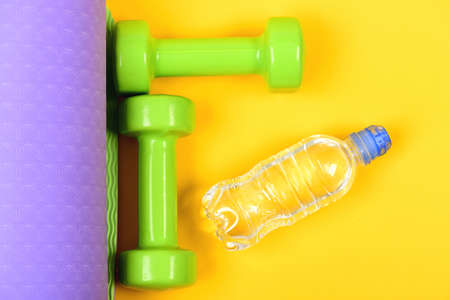 Dumbbells made of green plastic on purple and yellow background