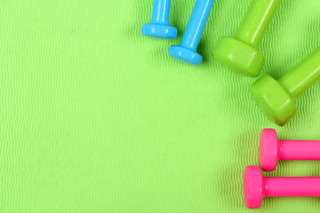Dumbbells made of pink, green and cyan blue plastic