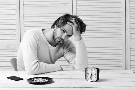 Man sits at wooden table with alarm clock and pills Stock Photo