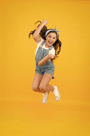 Totally happy. Energy inside. Feeling free. Summer holidays. Jump of happiness. Small girl jump yellow background. Enjoy freedom. Childrens day concept. Spirit of freedom. Active girl feel freedom