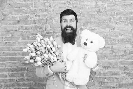 Nice bouquet. Flower for March 8. Love date. international holiday. Bearded man with tulip bouquet and bear. Womens day. Spring gift bouquet. Bearded man hipster with flower bouquet