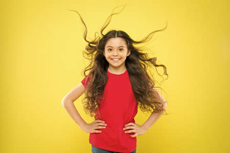 Wind can also damage hair. Girl adorable kid long wavy hair yellow background.