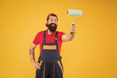 Room painting job. repair assistant in work uniform. engineer designer ready to paint wall.