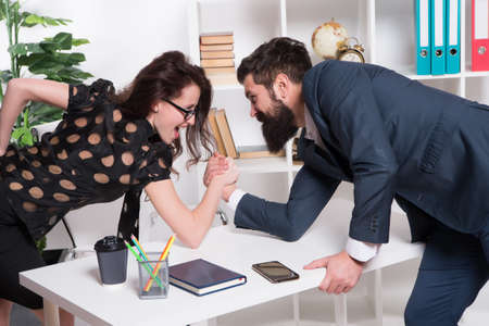 Prove how strong you are. Business partners get into armwrestling competition. Colleagues in competitive relations. Business relations. Professional couple relations. Relations between man and woman