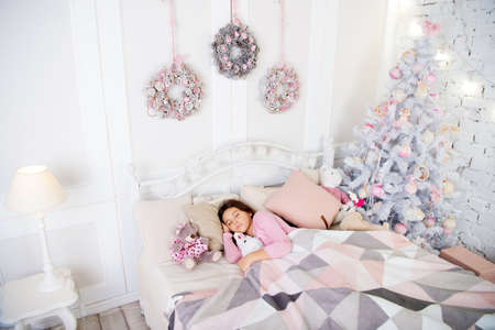 small girl sleeping at home. christmas family holiday. waiting for santa. Winter. The morning before Xmas. Sleep. happy new year. Who was naughty this year. little child girl with xmas present