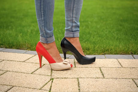 Legs in shoes and jeans on green grass background