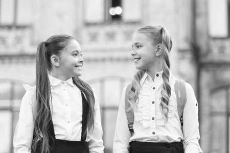 Soulmate friends. Cute schoolgirls with long ponytails looking charming. Ending of school year. Cheerful smart schoolgirls. Happy schoolgirls outdoors. Small schoolgirls wear school uniform