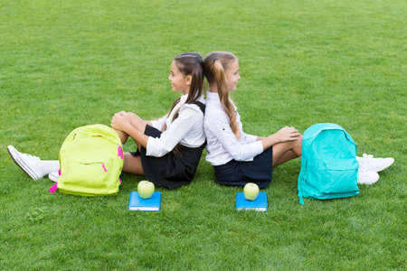 Come, relax and enjoy. School girls sit on green grass. Happy girls wear school uniform. Back to school. Beauty look of little girls. Small girls in pigtails. Hair salon. Beauty lies in healthy mind 写真素材