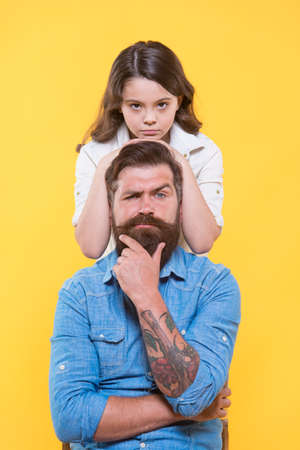 Father is idol of each child. Little daughter hug serious father. Small girl and father yellow background. Fathers day. Family values. Dad we will never be apart