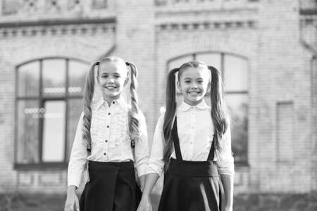 Lucky to meet each other. Cheerful smart schoolgirls. Happy schoolgirls outdoors. Small schoolgirls wear school uniform. Cute schoolgirls with long ponytails looking charming. Ending of school year