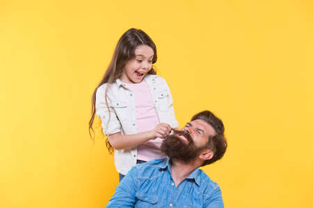 My father is hipster. Little girl pull hipster beard. Happy family yellow background. Hipster barbershop. Barber shop. Hair salon. The bushy beard is great Banque d'images