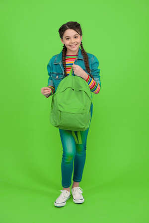 For the wanderlust in you. Happy kid hold backpack green background. Traveling and wanderlust. Wander and discover. Wanderlust concept. Summer vacation. Adventure and discovery. School holidays Фото со стока