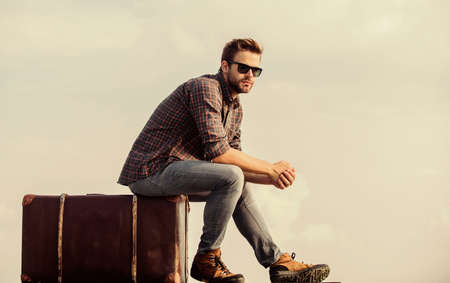 symbol of freedom. traveler wait for flight. Move. male fashion style. looking so trendy. businessman in glasses. business trip. macho man unshaven face sit on tour bag. man sky background