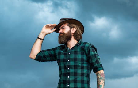 looking away. brutal hipster with moustache in hat. fashion model wear casual west clothes. male beauty standard. looking so trendy. Confident and handsome man. bearded man. texas brutal cowboy Stock Photo