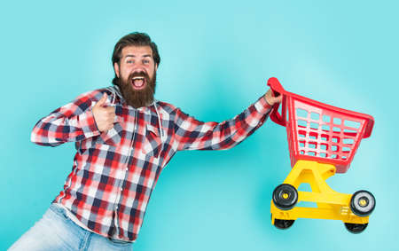 New arrivals. really busy housekeeper. perfect husband. need shopping list. bearded man go shopping with toy empty shopping cart. customer pushing cart. buyer in supermarket. empty toy trolley